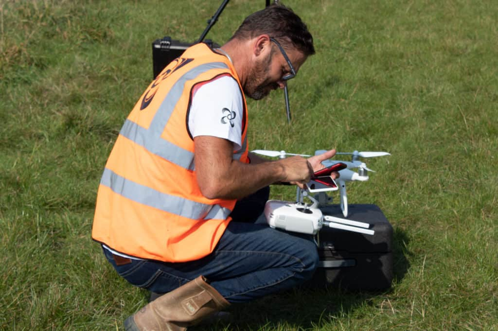 Sky revolutions pilot setting up drone filming